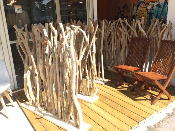 Une terrasse aménagée avec des cloisons en bois flotté